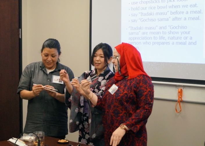 Women from Mexico and Iraqi learn to use chopsticks from Saori from Japan